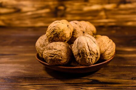 Ceramic plate with walnuts on rustic wooden table Stock Photo