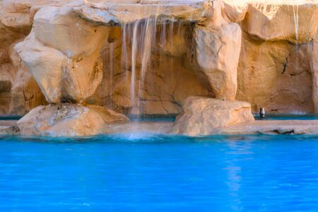 Small waterfall with turquoise water in hotel pool