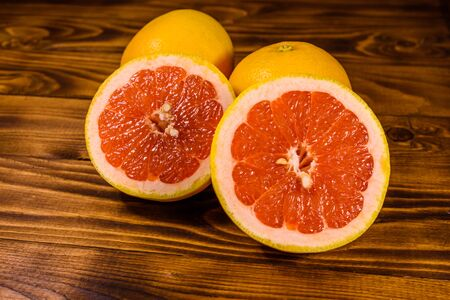 Ripe juicy grapefruit on rustic wooden table Stock Photo
