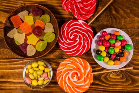 Different sweet candies on rustic wooden table. Top view