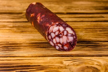 Smoked salami sausage on rustic wooden table Reklamní fotografie