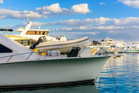 Closeup of white luxury yacht in sea harbor of Hurghada, Egypt. Marina with tourist boats on Red Sea