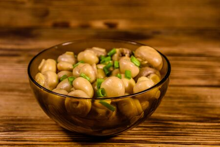 Glass bowl with canned mushrooms and green onion on rustic wooden table