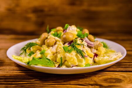 Salad with marinated mushrooms, eggs, red onion, boiled potato and mayonnaise on rustic wooden table