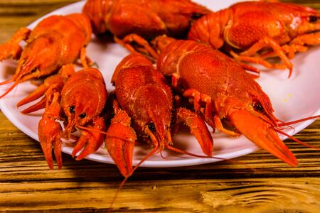 Plate with boiled crayfishes on rustic wooden table Banco de Imagens - 124997588