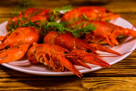 Plate with boiled crayfishes on rustic wooden table 스톡 콘텐츠 - 124997589