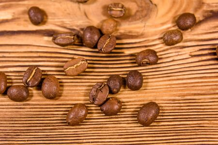 Scattered coffee beans on rustic wooden table. Top view Archivio Fotografico