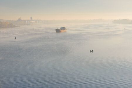 Cargo ship in fog on river Dnieper