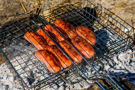 Sausages cooking in barbecue grill on campfire