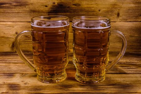 Two glasses of beer on rustic wooden table