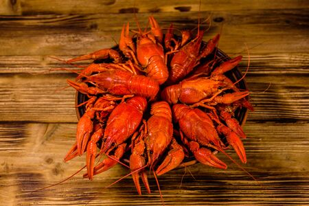 Plate with boiled crayfishes on rustic wooden table