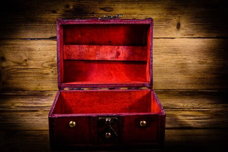 Opened vintage chest from red wood on rustic wooden background Stock Photo