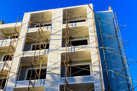 Construction of new modern residential building in Hurghada, Egypt. Wooden scaffolding around the building Stock Photo