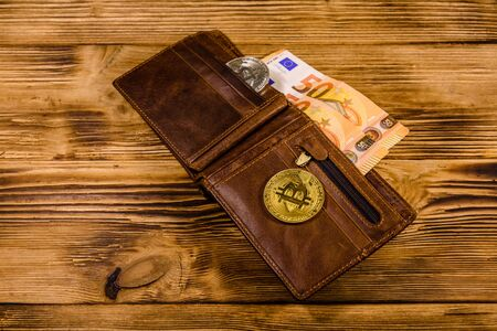 Brown leather wallet with fifty euro banknotes and bitcoins on wooden background