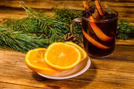 Cup of mulled wine with cinnamon, sliced orange and fir tree branches on rustic wooden table Stock Photo