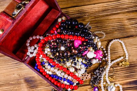 Old box of red wood full of jewelry. Treasure chest. Top view Stock Photo