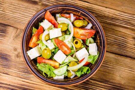 Ceramic plate with greek salad on rustic wooden table. Top view Stock Photo