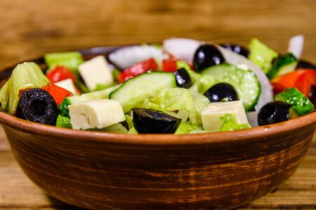 Ceramic plate with greek salad on rustic wooden table Stock Photo