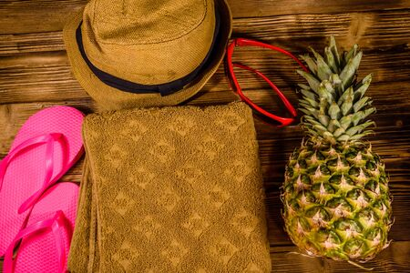 Pineapple, straw hat, towel, sunglasses and flip flops on rustic wooden table. Summer vacations. Top view Stock Photo