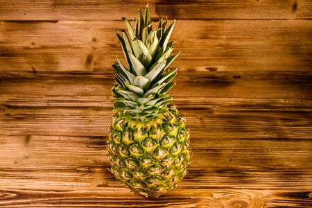 Whole ripe pineapple on rustic wooden table Stock Photo