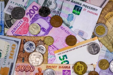 Multi currency background. Euro, american dollars, ukrainian hryvnias, egyptian pounds, russian roubles and different coins Stock Photo