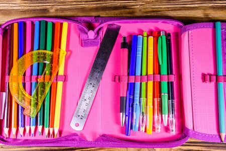 Different school stationeries (pens, pencils, ruler and protractor) in pink pencil box. Top view Stock Photo