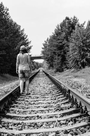 Lonely young woman on railway in forest Stock Photo