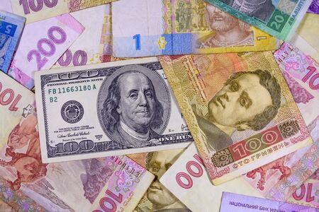 American one hundred dollars banknote on many ukrainian hryvnas