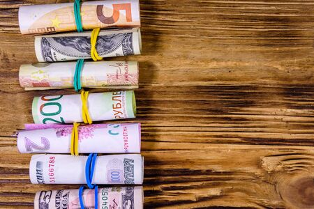 Many rolled up banknotes. Euro, american dollars, ukrainian hryvnias, egyptian pounds and russian roubles Stock Photo