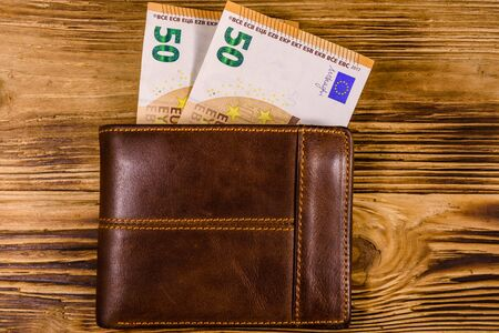 Brown leather wallet with fifty euro banknotes on wooden background. Top view 版權商用圖片
