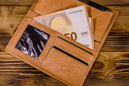 Brown leather wallet with fifty euro banknotes on wooden background. Top view Stockfoto