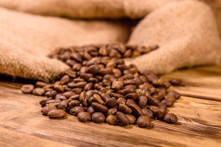 Sackcloth and scattered coffee beans on rustic wooden table