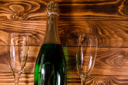 Bottle of champagne and two wineglasses on rustic wooden table. Top view