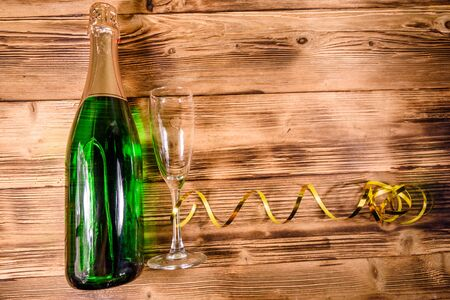Bottle of champagne and wineglass decorated with golden ribbon on rustic wooden table. Top view