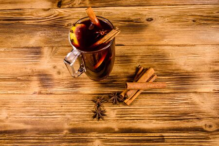 Cup of mulled wine with cinnamon on rustic wooden table Reklamní fotografie