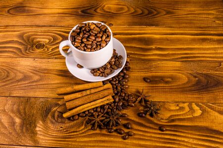 White cup filled with coffee beans, star anise and cinnamon sticks on rustic wooden table Reklamní fotografie