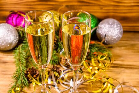 Two wineglasses with champagne and different christmas decorations on rustic wooden table