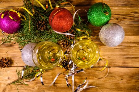 Two wineglasses with champagne and different christmas decorations on rustic wooden table. Top view