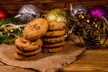 Stack of chocolate chip cookies on sackcloth in front of christmas decorations Reklamní fotografie