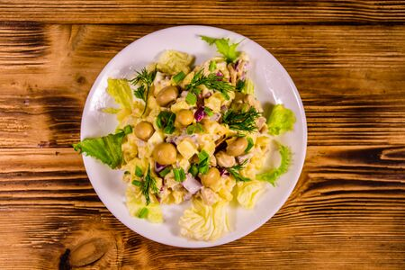 Salad with marinated mushrooms, eggs, red onion, boiled potato and mayonnaise on rustic wooden table. Top view Reklamní fotografie