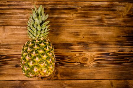 Whole ripe pineapple on rustic wooden table. Top view Reklamní fotografie
