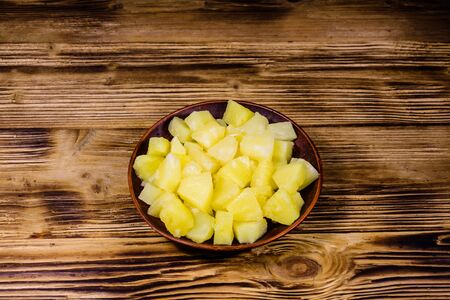 Ceramic plate with chopped canned pineapple on rustic wooden table Reklamní fotografie