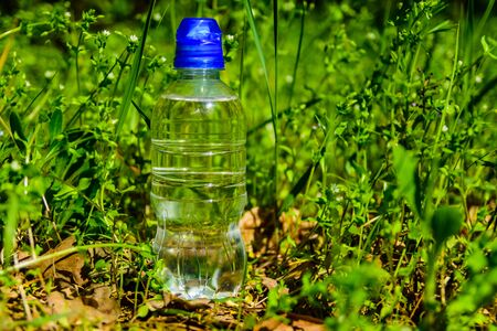 Plastic bottle with clear water in green grass