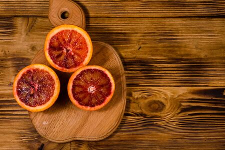 Cutting board with halved sicilian oranges on rustic wooden table. Top view Reklamní fotografie