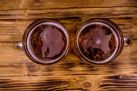 Two glasses of beer on rustic wooden table. Top view