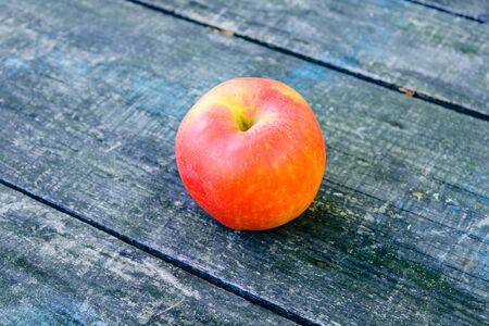 One ripe apples on rustic wooden table