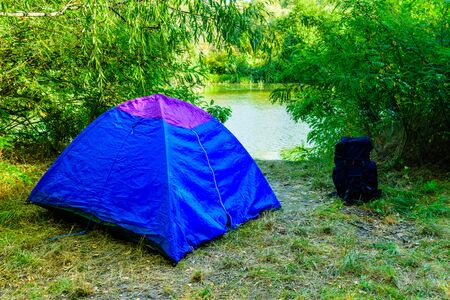 Blue tent and backpack in green forest on summer
