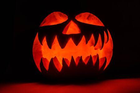 Spooky luminous halloween pumpkin on black background