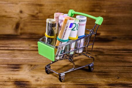 Many rolled up banknotes in small shopping cart. Euro, american dollars, ukrainian hryvnias, egyptian pounds and russian roubles