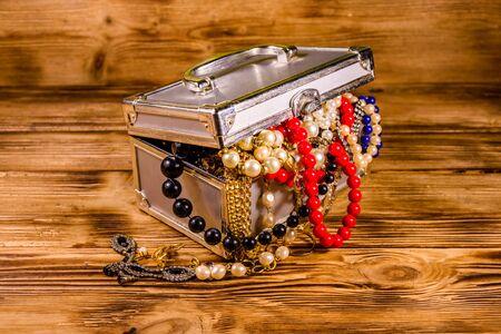 Aluminium case full of different jewelry on rustic wooden table Standard-Bild - 129419542